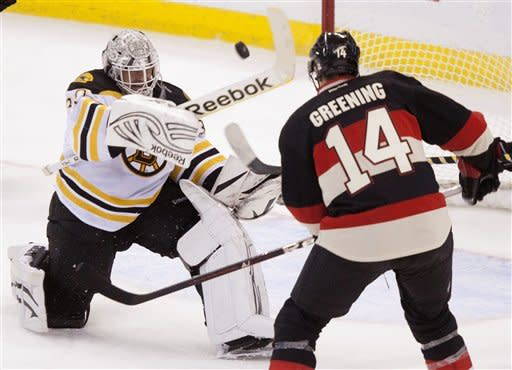 Boston Bruins goalie Tim Thomas, left, swings his stick to clear an airborne puck as he is pressured by Ottawa Senators left wing Colin Greening during second-period NHL hockey game action in Ottawa, Wednesday, Dec. 14, 2011. (AP Photo/The Canadian Press, Adrian Wyld)