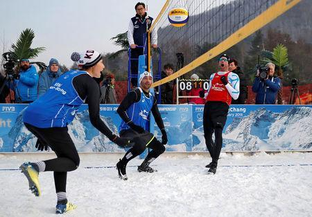 Pyeongchang 2018 Winter Olympics - Pyeongchang - South Korea – February 14, 2018. Nikolas Berger of Austria reacts as Kim Yeon-Koung of South Korea returns the ball watched by Giba Godoy of Brazil during an event promoting the Snow Volleyball hosted by the International Volleyball Federation (FIVB) and European Volleyball Confederation (CEV). REUTERS/Kim Hong-Ji
