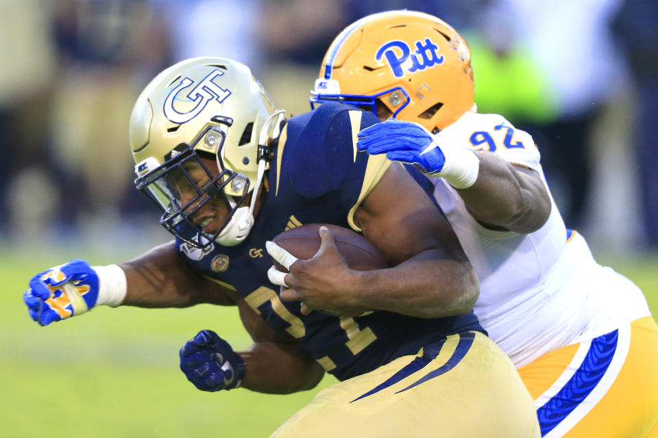 Defensive lineman Tyler Bentley of the Pittsburgh Panthers tackles running back Jordan Mason of the Georgia Tech