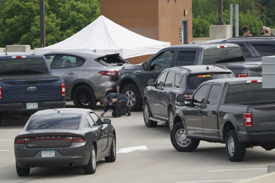 An investigator goes through the scene of crash believed to be part of an officer involved shooting on the top of a parking ramp in Minneapolis, Thursday June 3, 2021. One person was killed Thursday when authorities who were part of a task force that included U.S. Marshals fired their weapons after the person displayed a handgun in Minneapolis' Uptown neighborhood, the U.S. Marshals said. (Renee Jones Schneider/Star Tribune via AP)