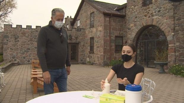 Jim Corcoran, owner of Ste. Anne's Spa in Grafton Ontario, looks on as an employee prepares to self-administer a rapid testing kit. He bought 3,000 kits after being told he wasn't eligible for ones from the province. (Doug Husby/CBC  - image credit)