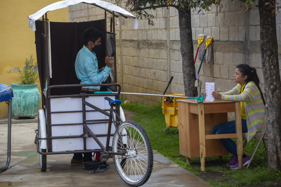 Gerardo Ixcoy teaches fractions to 14-year-old Brenda Morales, from his secondhand adult tricycle that he converted into a mobile classroom, in Santa Cruz del Quiche, Guatemala, Wednesday, July 15, 2020. The 27-year-old teacher deploys a sponge mop to serve as a safe distance reminder between him and his students, amid the new coronavirus pandemic. (AP Photo/Moises Castillo)