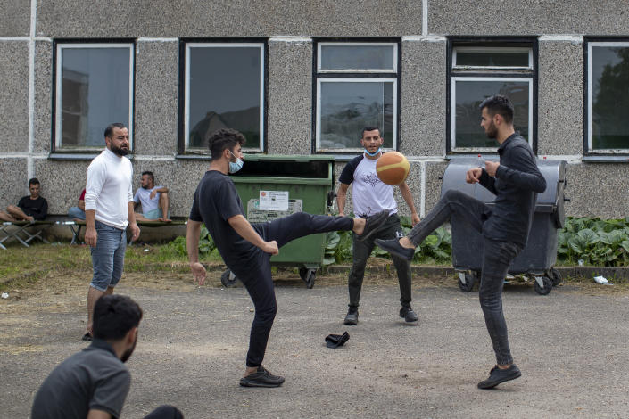 Migrants from Iraq, play with ball at the refugee camp in the village of Verebiejai, some 145km (99,1 miles) south from Vilnius, Lithuania, Sunday, July 11, 2021. Migrants at the school in the village of Verebiejai, about 140 kilometers (87 miles) from Vilnius, haven't been allowed to leave the premises and are under close police surveillance. Some have tested positive for COVID-19 and have been isolated in the building. (AP Photo/Mindaugas Kulbis)