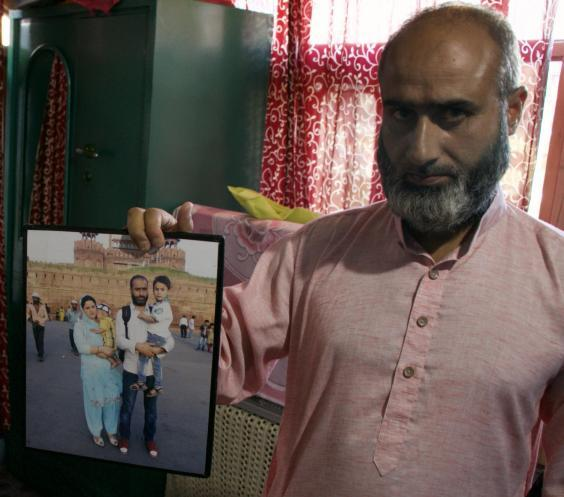Rafiq Shagoo holds a family photograph of his wife Fehmeeda Bano, 35, and their two sons. Fehmeeda died after inhaling tear gas during clashes (Zubair Sofi/The Independent)