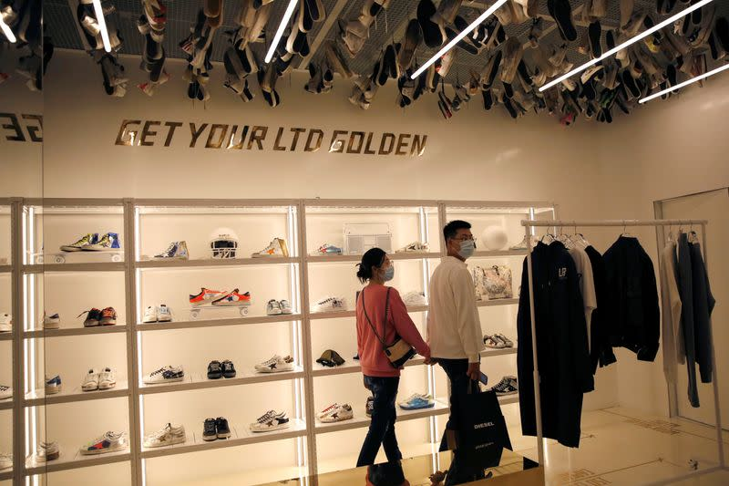 Customers wearing face masks following the COVID-19 outbreak are seen at Italian high fashion sneaker brand Golden Goose in Beijing