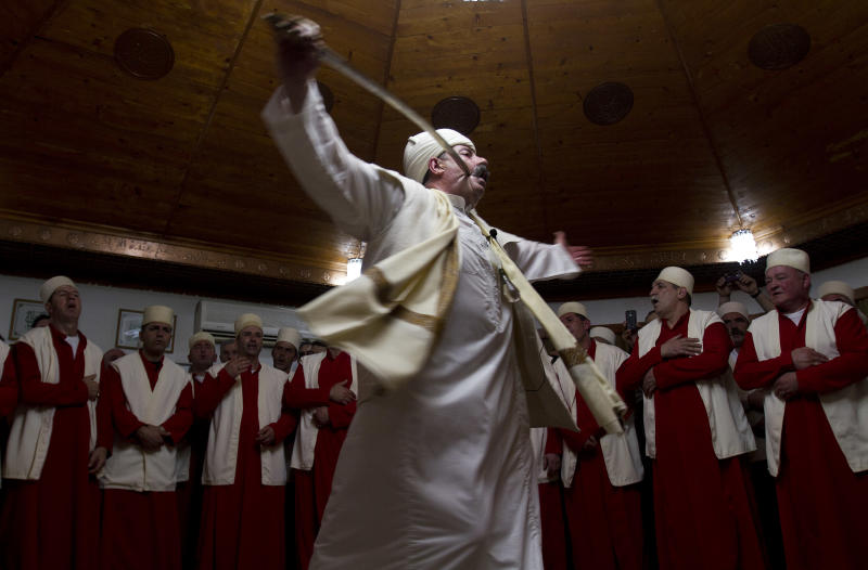 A sheikh leader of Kosovo followers of Sufism, a mystical form of Islam that preaches tolerance and a search for understanding, pierces himself with a sword during a ceremony marking Nowruz in the prayer room in the town of Gjakova on Thursday, March 21, 2013. The Kosovo dervish community carries on centuries-old mystical practices, such as self-piercing with needles and knives as a way to earn salvation and find the path to God. ( AP Photo / Visar Kryeziu )