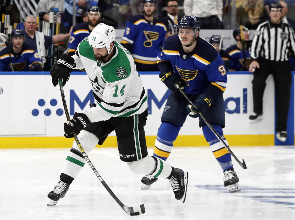 Dallas Stars' Jamie Benn (14) shoots the puck as St. Louis Blues' Sammy Blais (9) looks on during the second overtime period in Game 7 of an NHL second-round hockey playoff series, Tuesday, May 7, 2019, in St. Louis. (AP Photo/Jeff Roberson)
