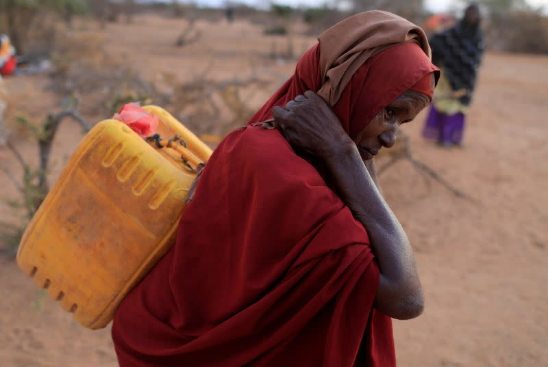 FILE PHOTO: An internally displaced woman from drought hit area carries a jerrycan of water as she walks towards her shelter at a makeshift settlement area in Dollow