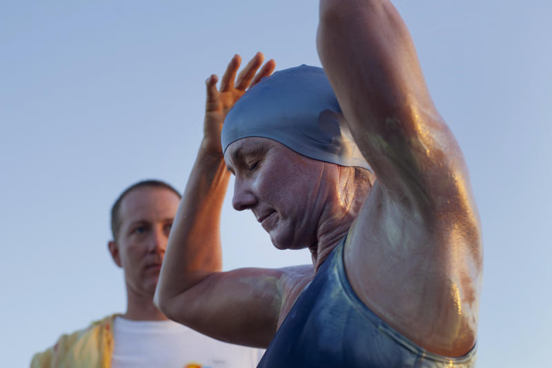 British-Australian swimmer Penny Palfrey adjusts her cap in preparation for her bid to complete a record swim from Cuba to Florida as her husband Chris stands by, in Havana, Cuba, Friday, June 29, 2012. Palfrey aims to be the first woman to swim the Straits of Florida without the aid of a shark cage. Instead she's relying on equipment that surrounds her with an electrical field to deter the predators. (AP Photo/Ramon Espinosa)