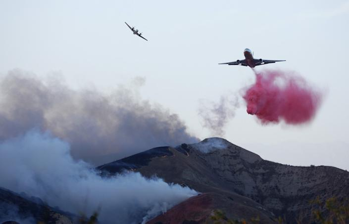 A fire spotter plane peels off after marking the drop location for an air tanker, which drops a cloud of pink retardant.