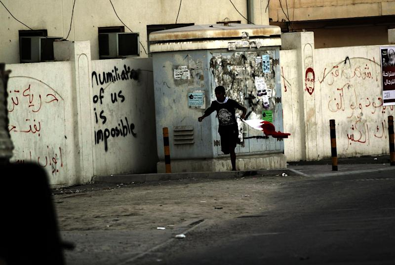 A Bahraini anti-government protester holding a national flag runs from riot police during clashes in Diraz, Bahrain, on Friday, Nov. 9, 2012. (AP Photo/Hasan Jamali)