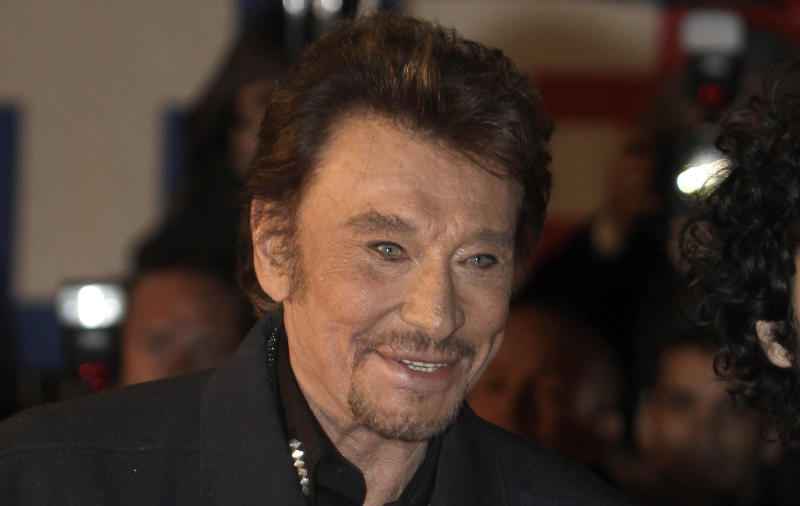 FILE - In this Saturday, Jan. 28, 2012 file photo, French singer Johnny Hallyday arrives at the Cannes festival palace, to take part in the NRJ Music awards ceremony, in Cannes, southeastern France. Hallyday, the French entertainer famed for his Elvis-like style and gravelly voice, was hospitalized for a severe case of bronchitis in Guadeloupe, his producer said Monday, Aug. 27, 2012. (AP Photo/Lionel Cironneau, File)