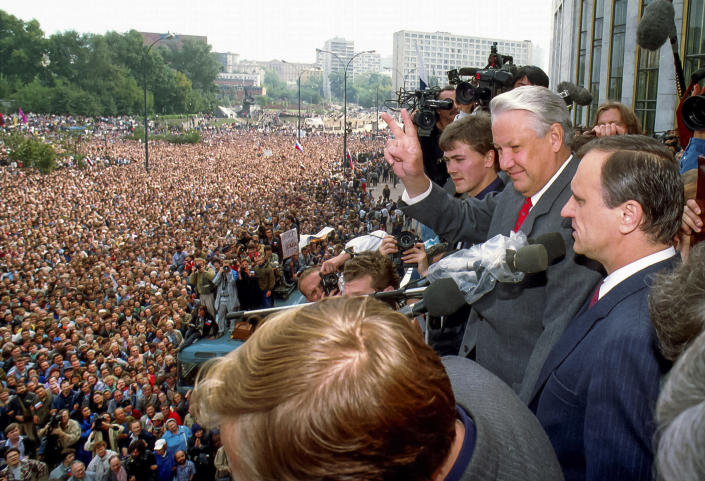 FILE - In this Thursday, Aug. 22, 1991 file photo, Russian Republic President Boris Yeltsin, second right, makes a V-sign to thousands of Muscovites, as his top associate Gennady Burbulis stands near, during a rally in front of the Russian federation building to celebrate the failed military coup in Moscow, Russia. When a group of top Communist officials ousted Soviet leader Mikhail Gorbachev 30 years ago and flooded Moscow with tanks, the world held its breath, fearing a rollback on liberal reforms and a return to the Cold War confrontation. But the August 1991 coup collapsed in just three days, precipitating the breakup of the Soviet Union that plotters said they were trying to prevent. (AP Photo/Alexander Zemlianichenko, file)