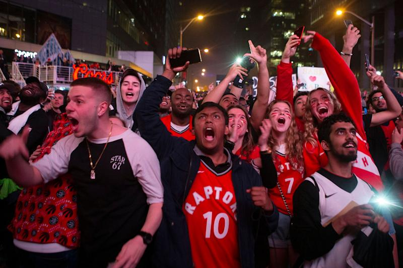 Toronto Raptors fans celebrate outside the arena in the closing seconds of the team's 100-94 win over the Milwaukee Bucks in Game 6 of the NBA basketball playoffs Eastern Conference finals Saturday, May 25, 2019, in Toronto. The Raptors advanced to the NBA Finals. (Chris Young/The Canadian Press via AP)