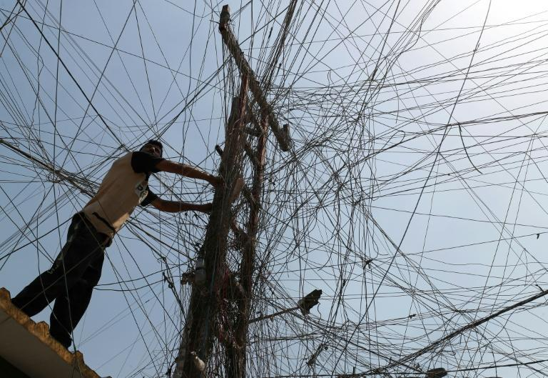 An Iraqi man connects overhead cables providing generator electricity to homes and businesses
