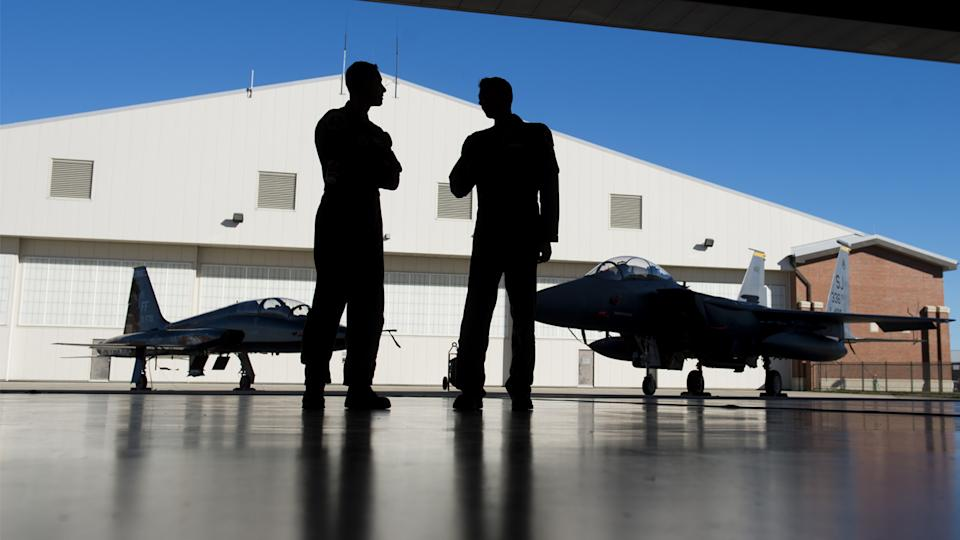 U.S. Air Force pilots inside a hangar alongside a F-15 fighter jet and a T-38 Talon trainer jet during an exercise in 2015. (Saul Loeb/AFP via Getty Images)