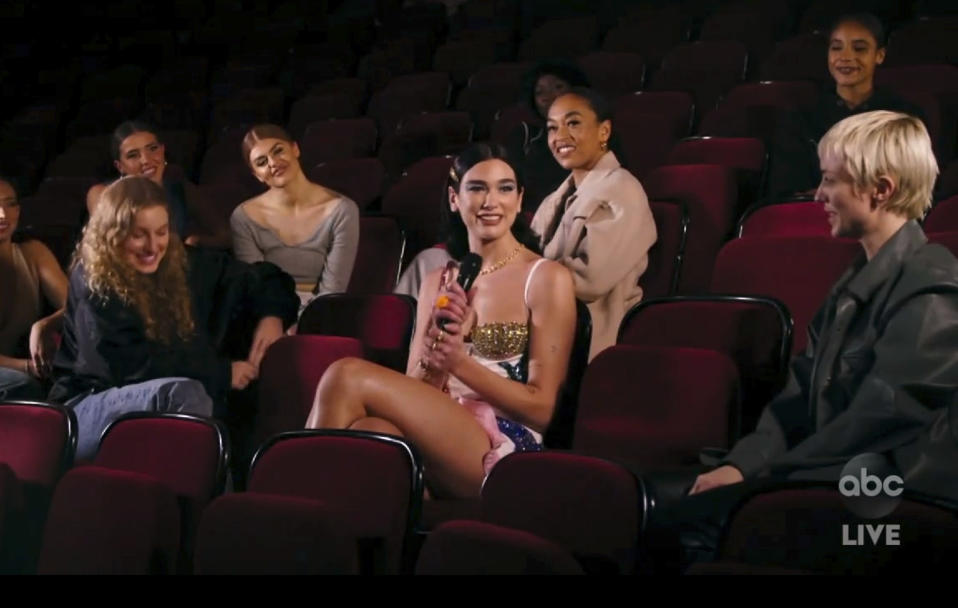 "In this screen shot provided by ABC on Sunday, Nov. 22, 2020, Dua Lipa, center, accepts the award for favorite pop/rock song for ""Don't Start Now"" at the American Music Awards at the Microsoft Theater in Los Angeles. (ABC via AP)"
