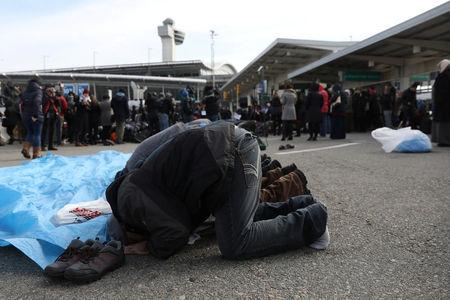 Men participate in prayers during an interfaith event and the Jummah prayer outside Terminal 4 at John F. Kennedy Airport in New York