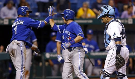 Toronto Blue Jays' J.P. Arencibia, center, is congratulated by teammate Emilio Bonifacio after his two-run home run during the ninth inning of a baseball game Monday, May 6, 2013, in St. Petersburg, Fla. The Blue Jays won 8-7. (AP Photo/Mike Carlson)
