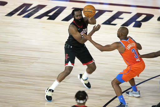 Houston Rockets' James Harden, left, passes the ball as Oklahoma City Thunder's Chris Paul (3) defends during the second half of an NBA basketball first round playoff game Saturday, Aug. 29, 2020, in Lake Buena Vista, Fla. (AP Photo/Ashley Landis)