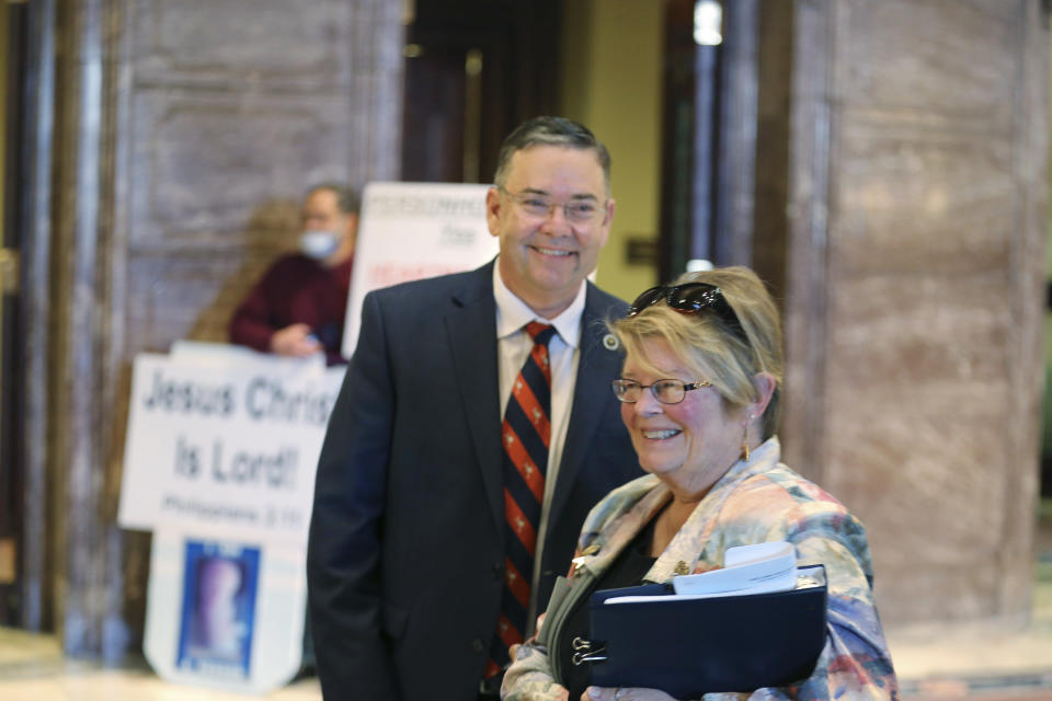 South Carolina Rep. John McCravy, left, and South Carolina Citizens for Life Executive Director Holly Gatling, right, talk after the state Senate approved a bill that would likely ban almost all abortions in the state on Thursday, Jan. 28, 2021, in Columbia, S.C. McCravy has worked to pass similar bills in the House. (AP Photo/Jeffrey Collins).