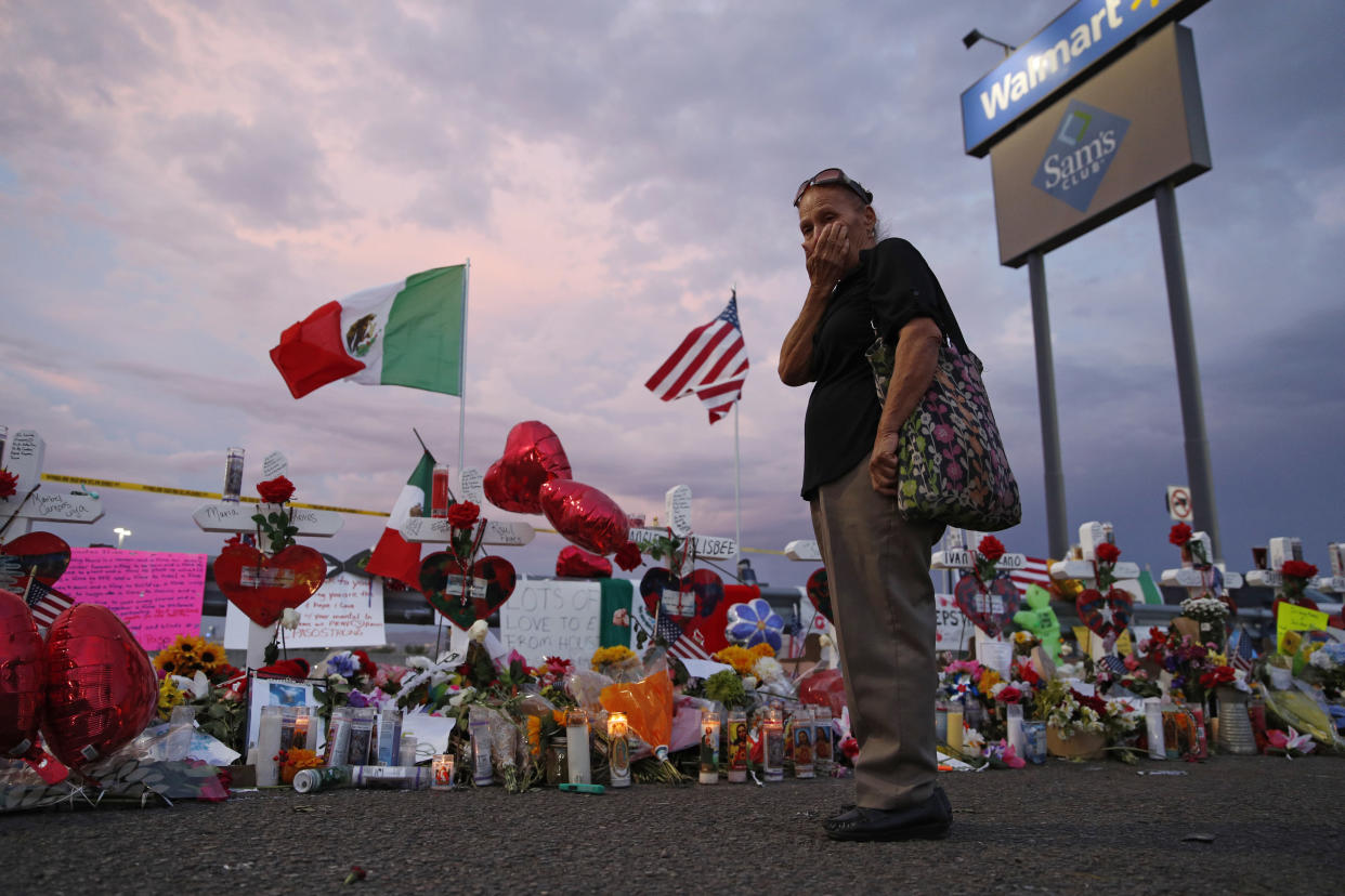 A woman wipes tears from her face as she visits a makeshift memorial near the scene of a mass shooting at a Walmart in El Paso, Texas. (AP Photo/John Locher)