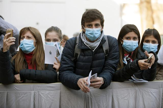 Young people are pictured wearing masks in Rome on 26 February. Italy has had more than 41,000 confirmed coronavirus cases since the outbreak was identified. (Getty Images)