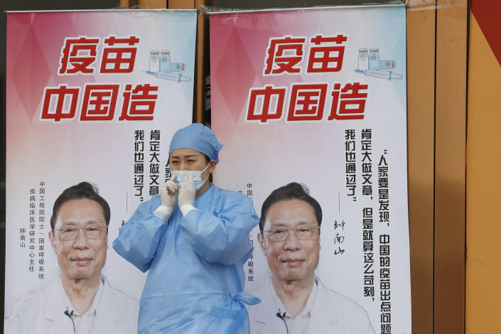 "A medical worker adjusts her mask near propaganda boards showing famed Chinese medical expert Zhong Nanshan and the words ""Vaccine China Made"" outside vaccination center in Beijing Friday, April 9, 2021. In a rare admission of the weakness of Chinese coronavirus vaccines, the country's top disease control official says their effectiveness is low and the government is considering mixing them to give them a boost. (AP Photo/Ng Han Guan)"