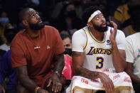 Los Angeles Lakers' LeBron James, left, sits on the bench with forward Anthony Davis during the first half of a preseason NBA basketball game against the Brooklyn Nets Sunday, Oct. 3, 2021, in Los Angeles. (AP Photo/Mark J. Terrill)