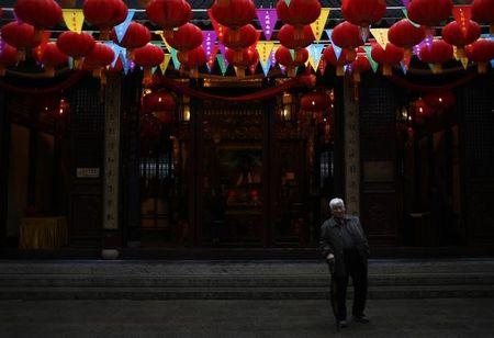A man walks under Chinese New Year decorations as he visit the Old City God Temple in Yuyuan Garden in Shanghai