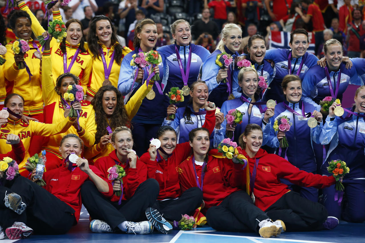 Medallists from Norway (blue), Montenegro (red) and Spain (yellow) pose during the victory ceremony for the women's handball final during the London 2012 Olympic Games at the Basketball Arena August 11, 2012. Norway won the gold, Montenegro silver and Spain the bronze.      REUTERS/Marko Djurica (BRITAIN  - Tags: SPORT HANDBALL OLYMPICS)
