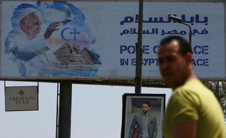 A man looks on near a billboard ahead of Pope Francis' visit in Cairo, Egypt April 26, 2017. REUTERS/Amr Abdallah Dalsh