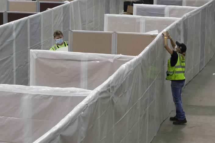 FILE — In this April 18, 2020 file photo sheeting is placed on partitions installed between beds as work is performed to turn the Sleep Train Arena into a 400 bed emergency field hospital to help deal with the coronavirus , in Sacramento, Calif. California spent nearly $200 million to set up, operate and staff alternate care sites that ultimately provided little help when the state's worst coronavirus surge spiraled out of control last winter, forcing exhausted hospital workers to treat patients in tents and cafeterias. (AP Photo/Rich Pedroncelli, File)