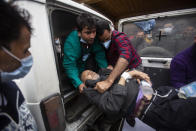 A Kashmiri man injured in an attack is brought for treatment at a hospital in Srinagar, Indian controlled Kashmir, Monday, March. 29, 2021. Gunmen killed an elected official of India's ruling party and a policeman in disputed Kashmir on Monday, police said. (AP Photo/Mukhtar Khan)