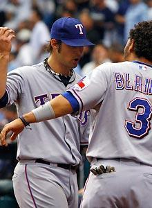 Rangers starting pitcher C.J. Wilson (left) is congratulated by Andres Blanco