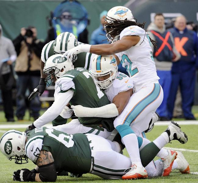 New York Jets quarterback Geno Smith, center left, is sacked by Miami Dolphins defensive end Olivier Vernon, center right, during the first half of an NFL football game Sunday, Dec. 1, 2013, in East Rutherford, N.J. (AP Photo/Bill Kostroun)