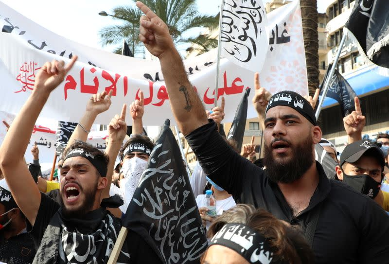 Demonstrators gestures during a protest against the cartoon publications of Prophet Mohammad in France and comments by the French President Emmanuel Macron, in Beirut