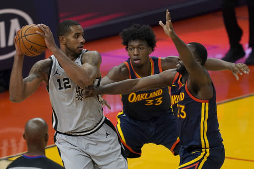 San Antonio Spurs center LaMarcus Aldridge (12) is defended by Golden State Warriors center James Wiseman, middle, and forward Draymond Green during the first half of an NBA basketball game in San Francisco, Wednesday, Jan. 20, 2021. (AP Photo/Jeff Chiu)