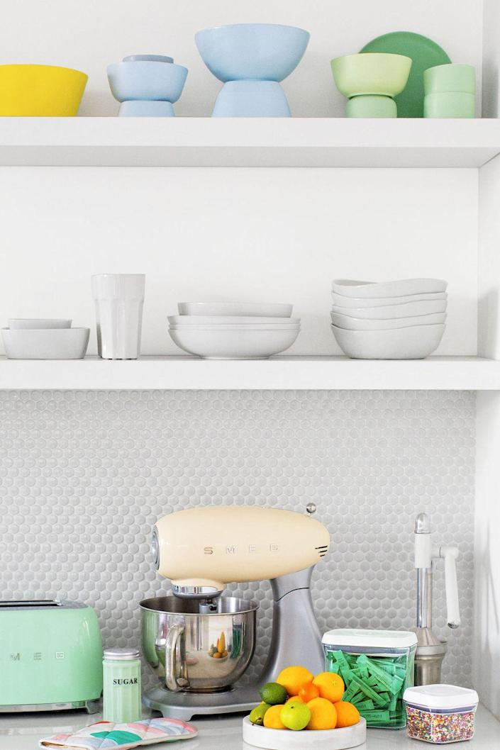 """<p>Cluttered countertops are a chef's nightmare. Grouping kitchen gear by color lets you reap the benefits of an organized kitchen without the stress of visible clutter. Amp things up a notch by taking everything off the counters and storing them on open shelves.</p><p><strong>RELATED:</strong> <a href=""""https://www.goodhousekeeping.com/home/organizing/tips/g1397/small-kitchen-storage/"""" rel=""""nofollow noopener"""" target=""""_blank"""" data-ylk=""""slk:20 Smart Storage Tricks for a Small Kitchen"""" class=""""link rapid-noclick-resp"""">20 Smart Storage Tricks for a Small Kitchen</a></p>"""
