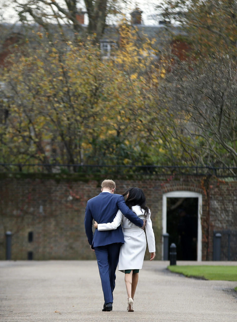 """FILE - In this Monday Nov. 27, 2017 file photo Britain's Prince Harry and Meghan Markle walk away after posing for the media in the grounds of Kensington Palace in London. In a stunning declaration, Britain's Prince Harry and his wife, Meghan, said they are planning """"to step back"""" as senior members of the royal family and """"work to become financially independent."""" A statement issued by the couple Wednesday, Jan. 8, 2020 also said they intend to """"balance"""" their time between the U.K. and North America. (AP Photo/Alastair Grant, File)"""