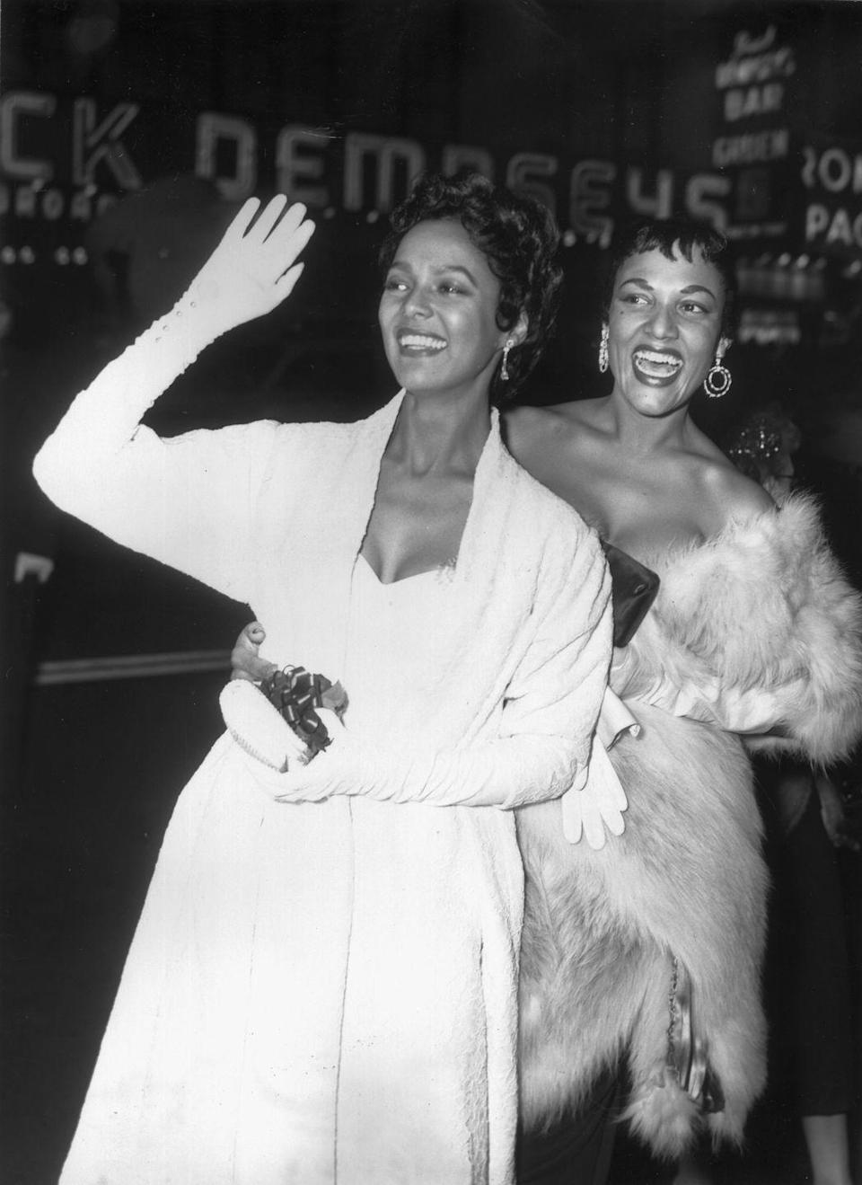 <p>Dorothy Dandridge and her sister, Vivian Dandridge, walking the red carpet in evening gowns, opera gloves, and an opulent fur sole.</p>