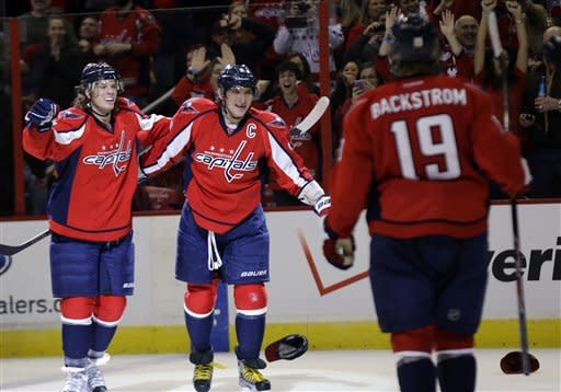 Washington Capitals left wing Alex Ovechkin, center, from Russia, celebrates with defenseman John Carlson, left, as center Nicklas Backstrom (19) from Sweden, comes to join in, after Ovechkin's third goal of the game during the third period of an NHL hockey game against the New Jersey Devils Saturday, Feb. 23, 2013 in Washington. Ovechkin had three goals, and the Capitals won 5-1. (AP Photo/Alex Brandon)