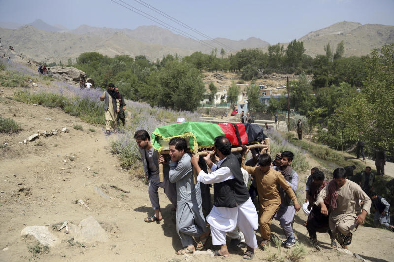 Relatives carry the coffin of Mohammad Akhtar, the driver for Agence France Presse news agency, who was killed in yesterday's suicide attack, during his burial ceremony in Guldara district, north of capital Kabul, Afghanistan, Monday, July 23, 2018. An Afghan spokesman said there has been a large explosion near the Kabul airport shortly after the country's controversial first vice president landed on his return from abroad. Gen. Abdul Rashid Dostum and members of his entourage were unharmed in the explosion on Sunday, which took place as his convoy had already left the airport. (AP Photo/Rahmat Gul)