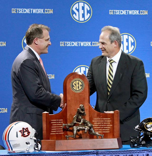 Auburn coach Gus Malzahn, left, and Missouri coach Gary Pinkel shake hands behind the Southeastern Championship trophy during a press conference the day before the SEC football championship game, at the Georgia Dome, Friday, Dec. 6, 2013, in Atlanta, Ga., (AP Photo/Atlanta Journal-Constitution, Jason Getz)