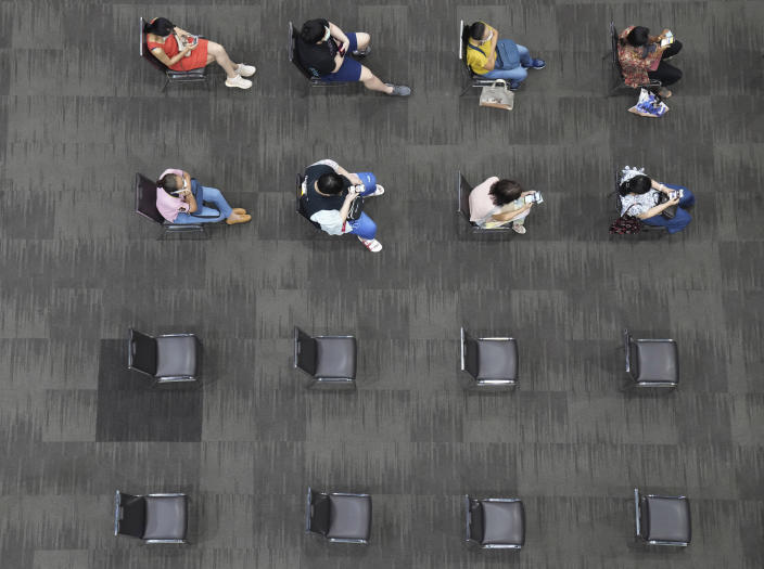 People sit and wait after receiving the AstraZeneca COVID-19 vaccine to be sure of no side effects at Paragon shopping mall in Bangkok, Thailand, Monday, June 7, 2021. Health authorities in Thailand on Monday began their much-anticipated mass rollout of locally produced AstraZeneca vaccine, but it appeared that supplies were falling short of demand from patients who had scheduled vaccinations for this week. (AP Photo/Sakchai Lalit)