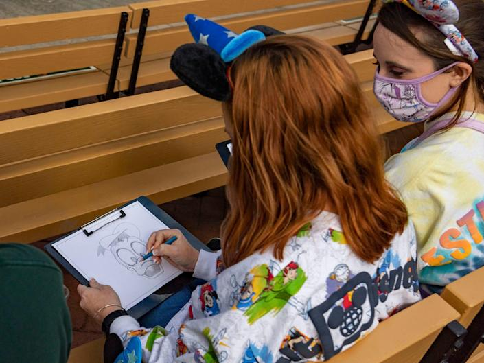 two disney guests drawing characters during the animation experience