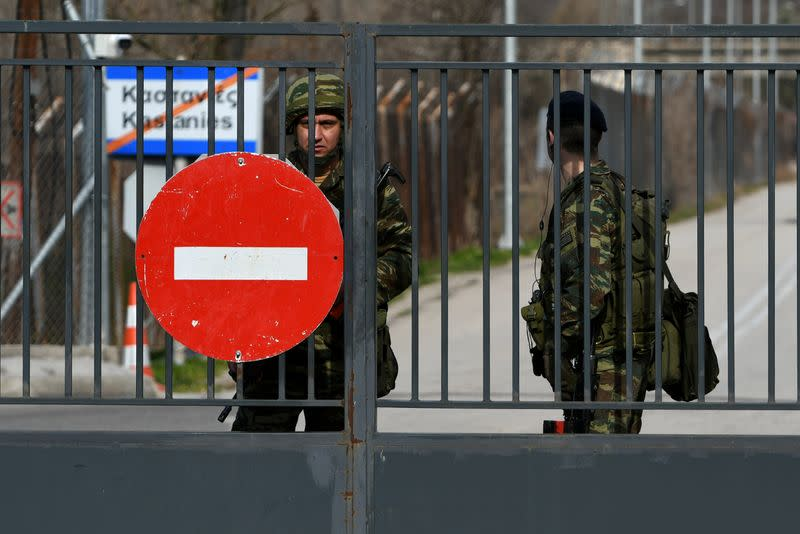 Greek soldiers stand guard at the closed Kastanies border crossing with Turkey's Pazarkule, in the region of Evros