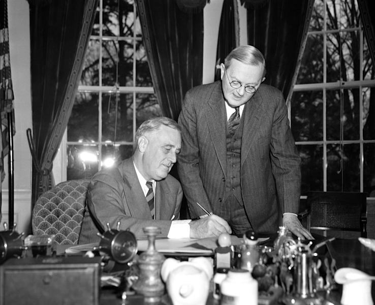 FILE - In this April 2, 1940 file photo, William L. Austin, director of the U.S. Census Bureau, right, helps President Franklin D. Roosevelt fill out the large form at the White House in Washington. Interest in the newly released 1940 U.S. census is so great that the government website with the information was nearly paralyzed on Monday, April 02, 2012, shortly after the records became available to the public for the first time. (AP Photo, File)
