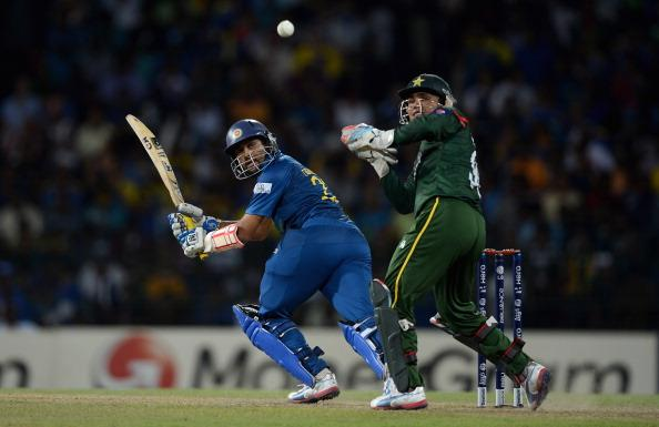 COLOMBO, SRI LANKA - OCTOBER 04:  Tillakaratne Dilshan of Sri Lanka hits past Pakistan wicketkeeper Kamran Akmal during the ICC World Twenty20 2012 Semi Final between Sri Lanka and Pakistan at R. Premadasa Stadium on October 4, 2012 in Colombo, Sri Lanka.  (Photo by Gareth Copley/Getty Images)