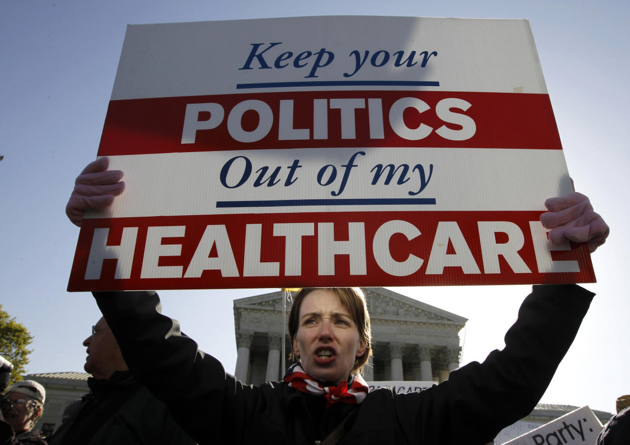 Amy Brighton from Medina, Ohio, who opposes health care reform, rallies in front of the Supreme Court in Washington, Tuesday, March 27, 2012, as the court continues arguments on the health care law signed by President Barack Obama. (AP Photo/Charles Dharapak)